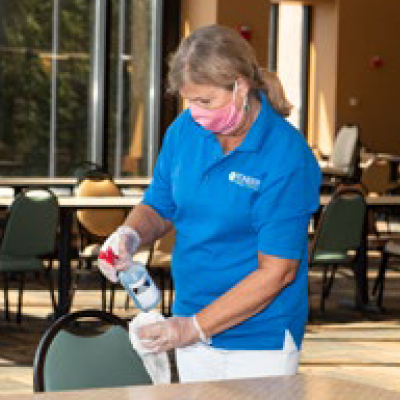 Woman cleaning tables and chairs in dining hall