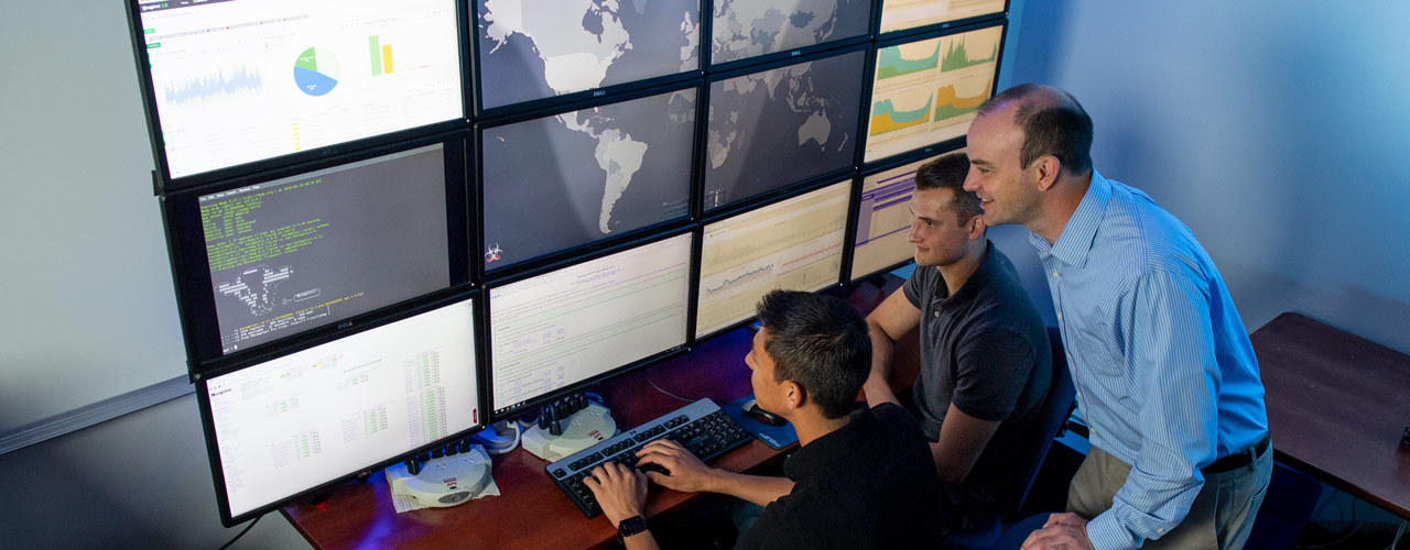 Faculty member and students looking at a bank of computer monitors showing graphs and worldwide cyber activity