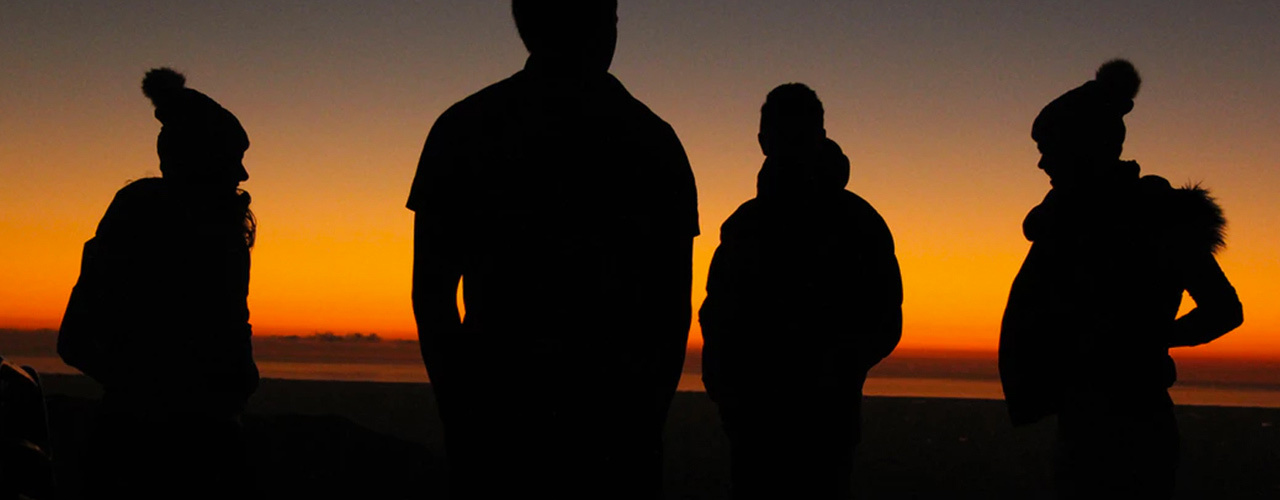 silhouettes of people standing outside with a yellow and orange sunset in the background