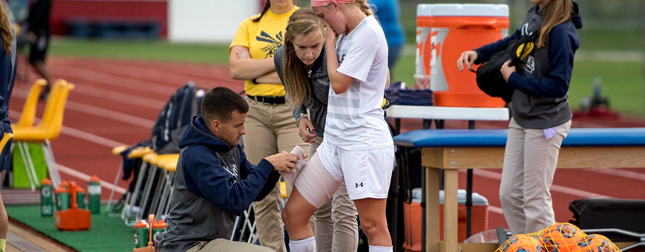 Male athletic training student bandages an athlete