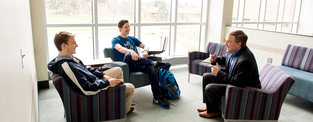 Bible professor casually chats with two students
