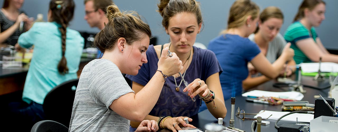Two female biology students inject solution into test tube