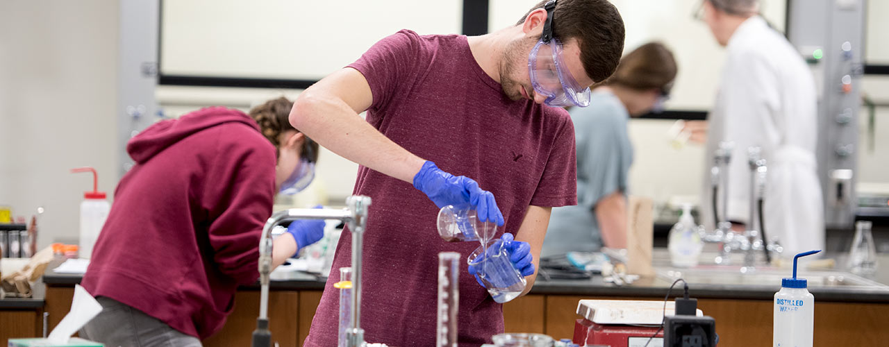 Male chemistry student pours liquid from beaker