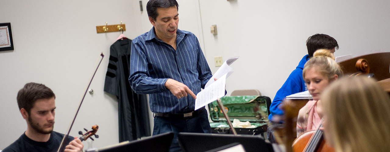 Music composition professor points to a sheet of music