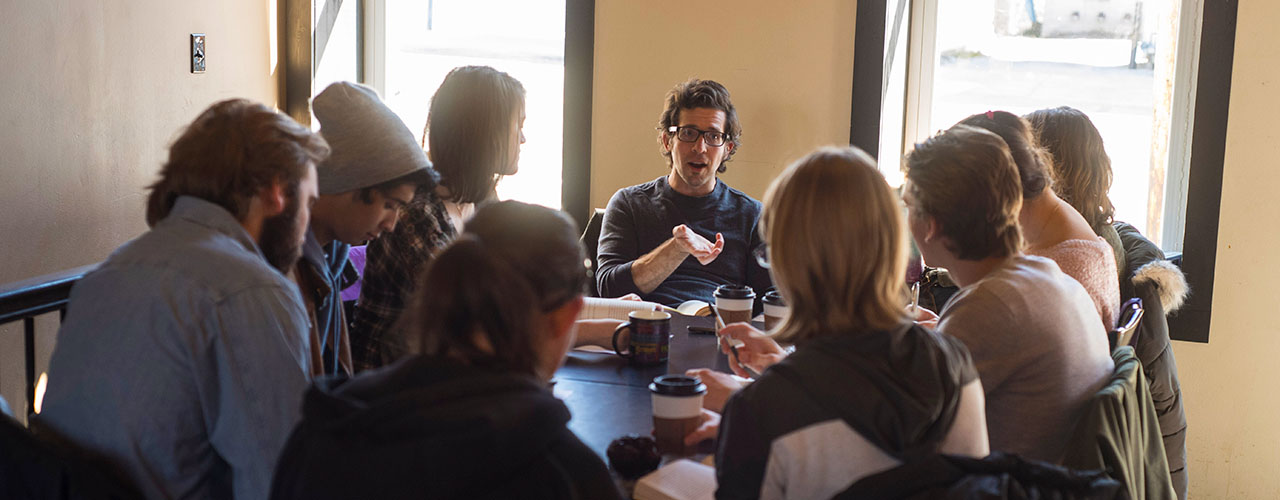 Nine individuals discuss together at a creative writing workshop, with their books open and coffee in hand.