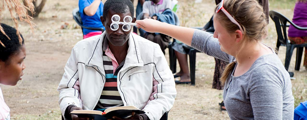 Female Nursing student helps African male with eye test
