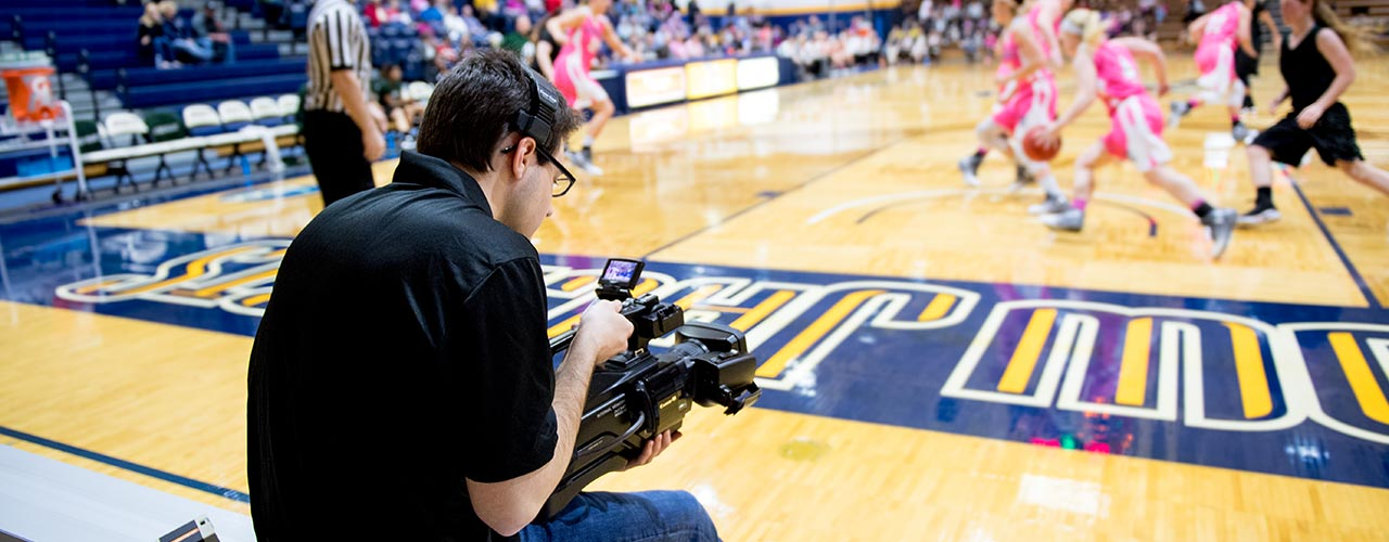 Male student films women's basketball game