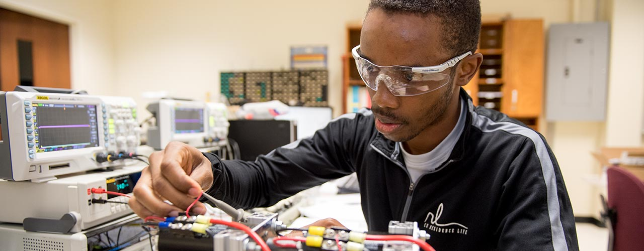 Male electrical engineer with safety glasses assembles a circuit