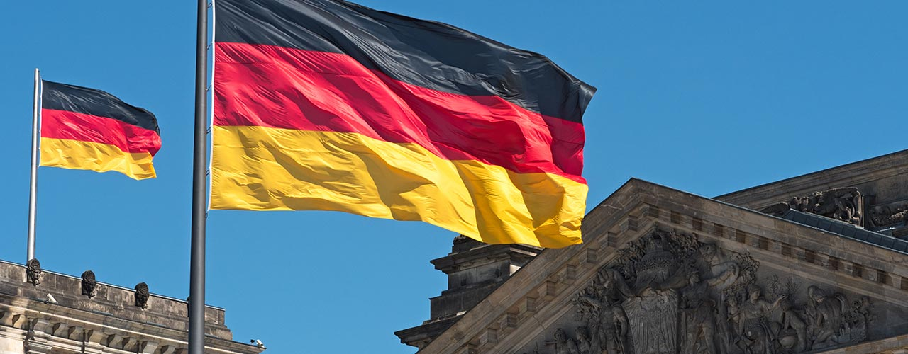 German flag waves next to historic building