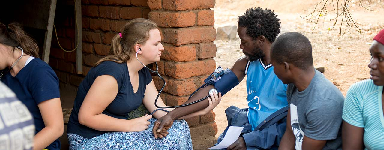 Female nurse takes the blood pressure of an African male