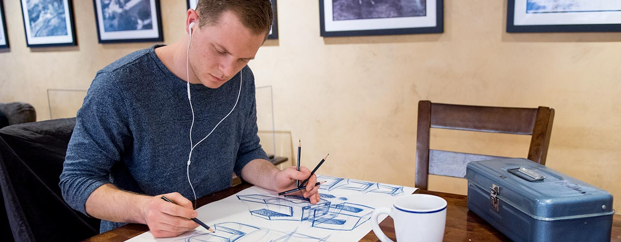 Male industrial design student drafts a design while listening to music