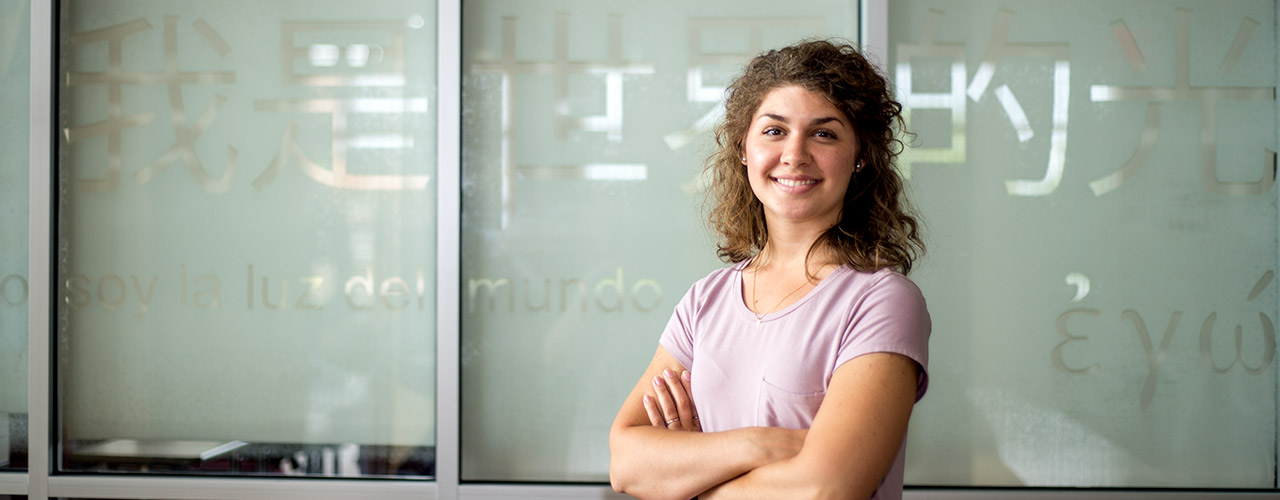 Student stands in front of frosted glass with different languages painted on it