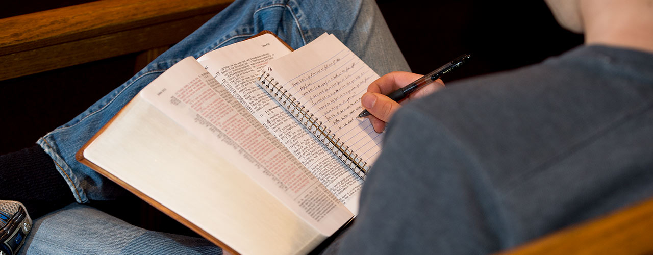 Male studies the Bible and takes notes