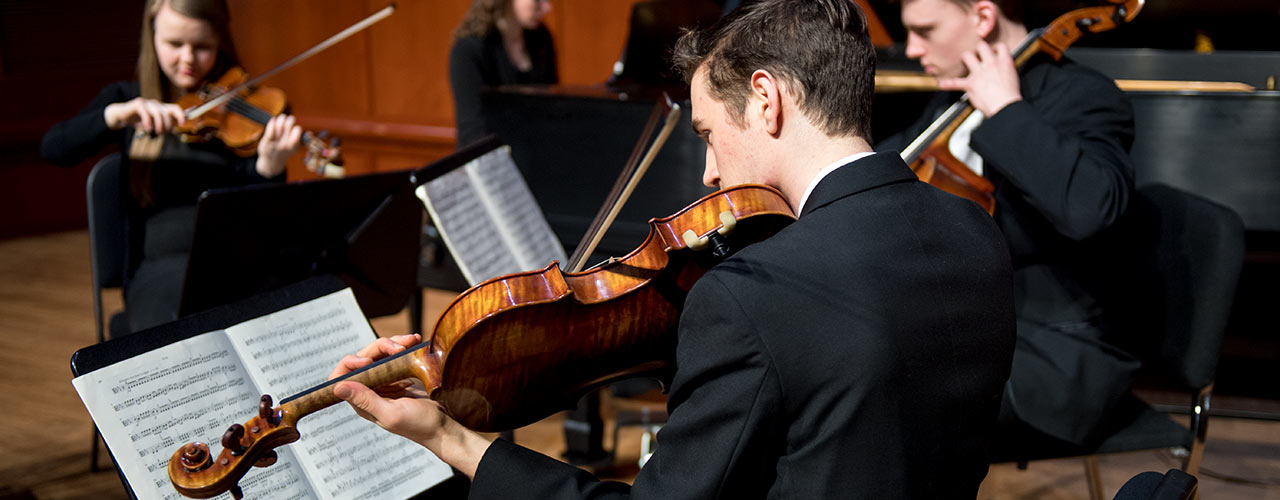 Male performance major plays the violin in an orchestra