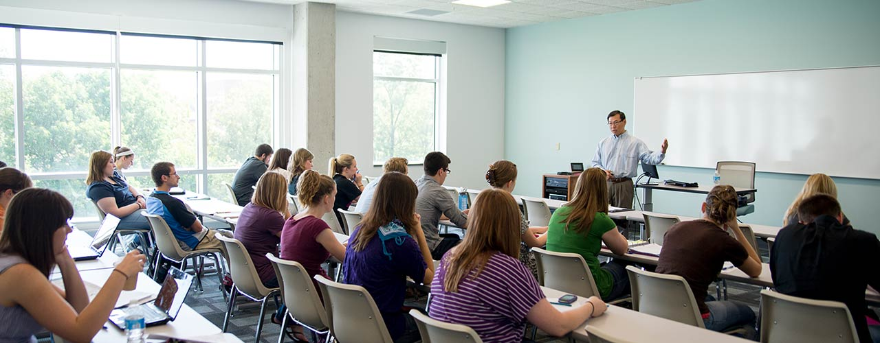 Male psychology professor lectures in front of his class