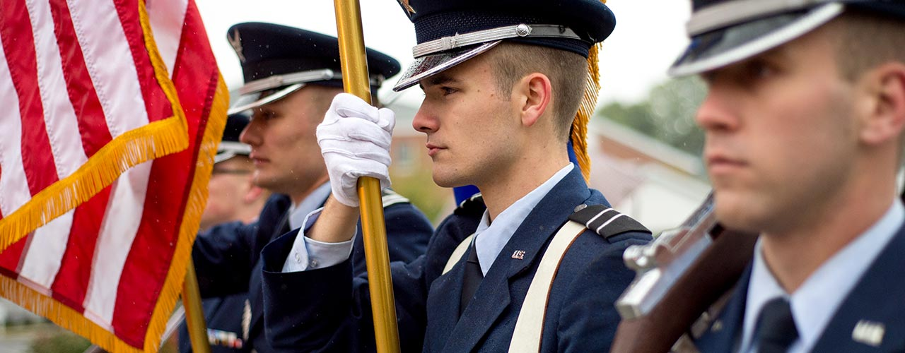 Male ROTC students stand at attention holding American flag