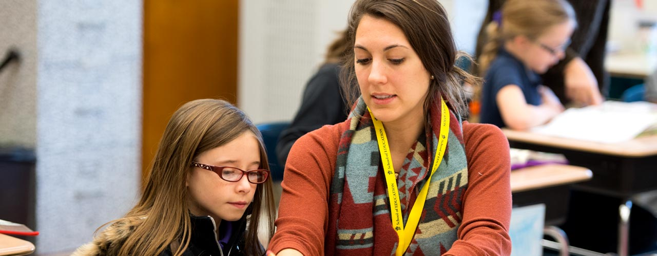 Female education student teaching a little girl at school