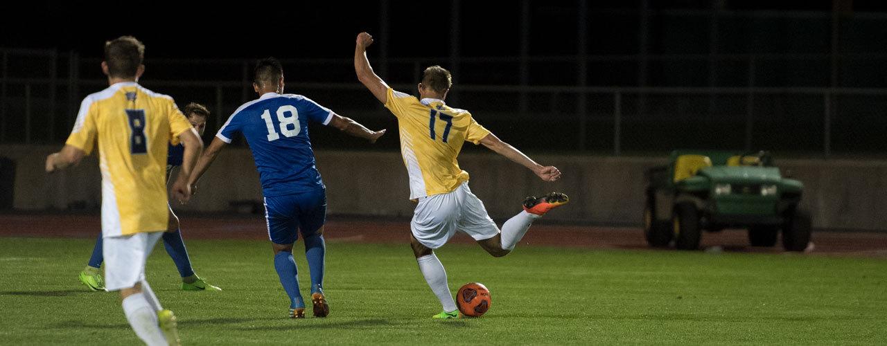 Soccer player kicks soccer ball