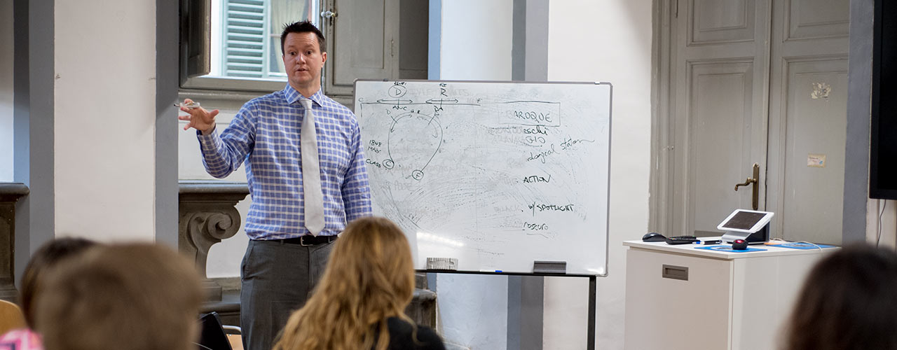 Male history professor using whiteboard to illustrate concepts to the class