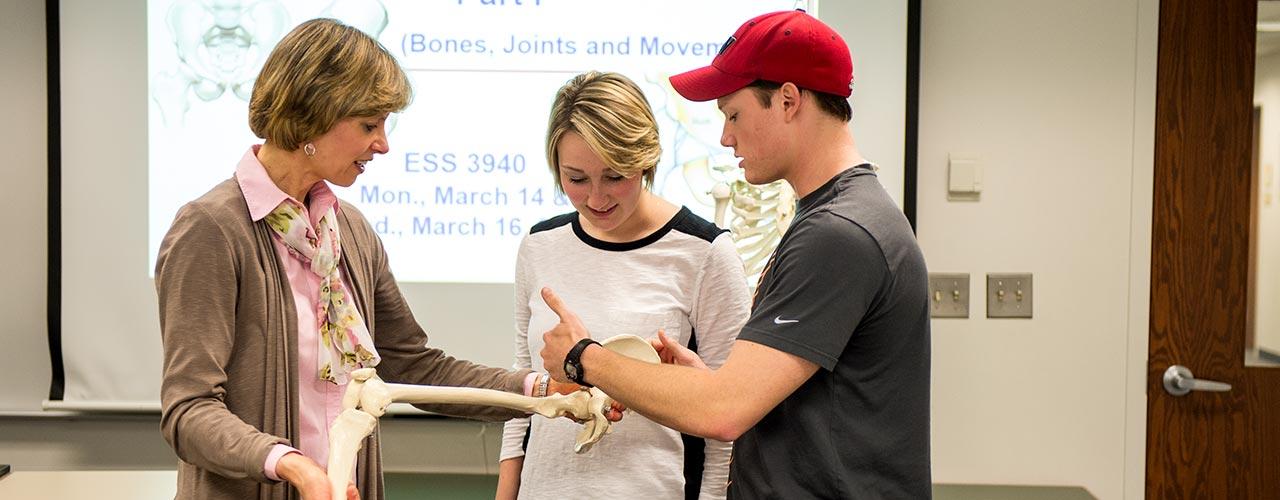 Professor and two students examine a bone