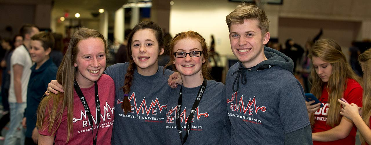 Group of students wearing lanyards smile while enjoying Cedarville's Revive event