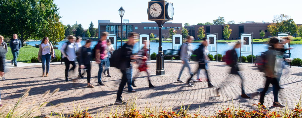 Rushing students walking by the clock outside of the SSC
