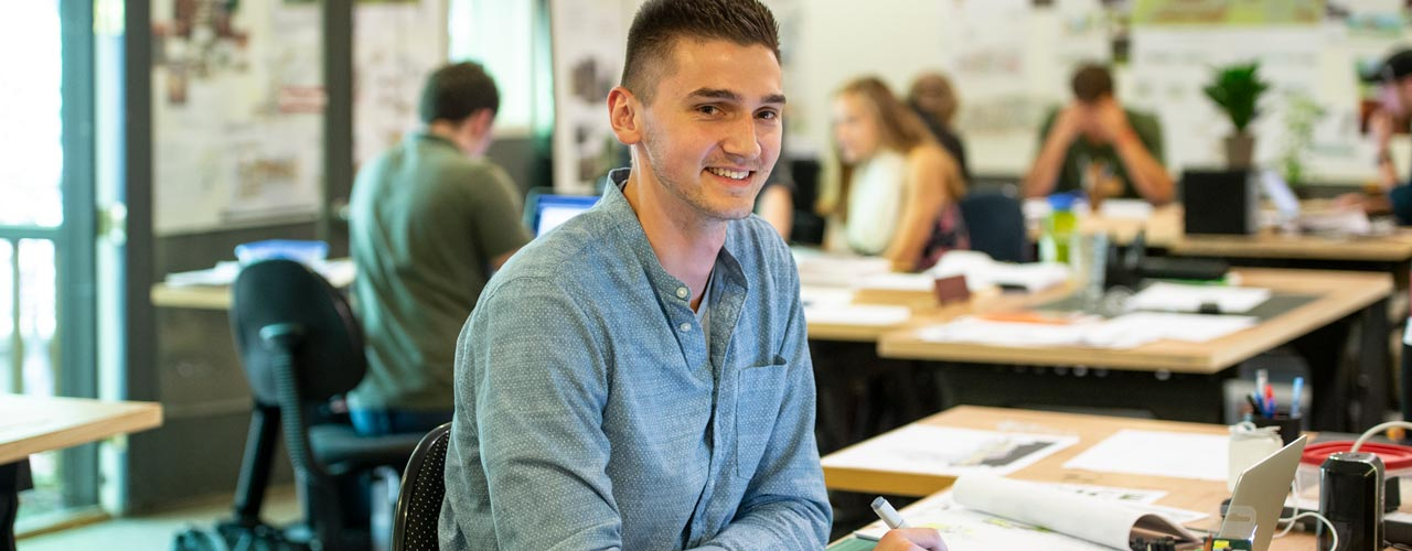 White male college student sitting at desk, looking at camera and smiling