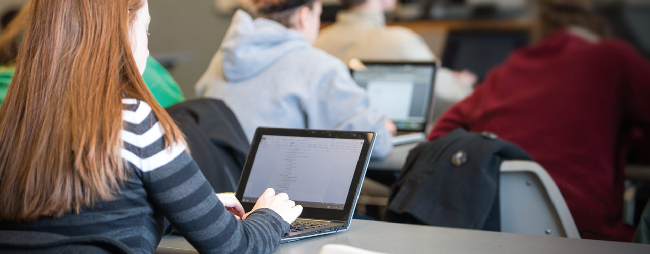 Female student takes notes on laptop in class