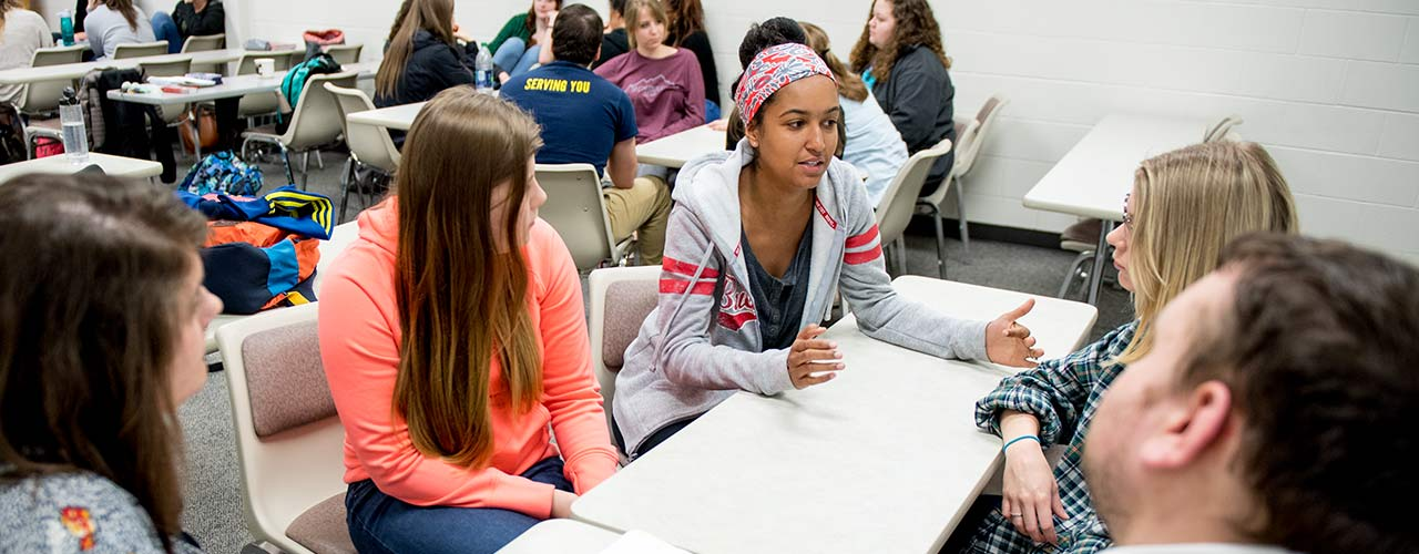 Female social work students discuss around a table