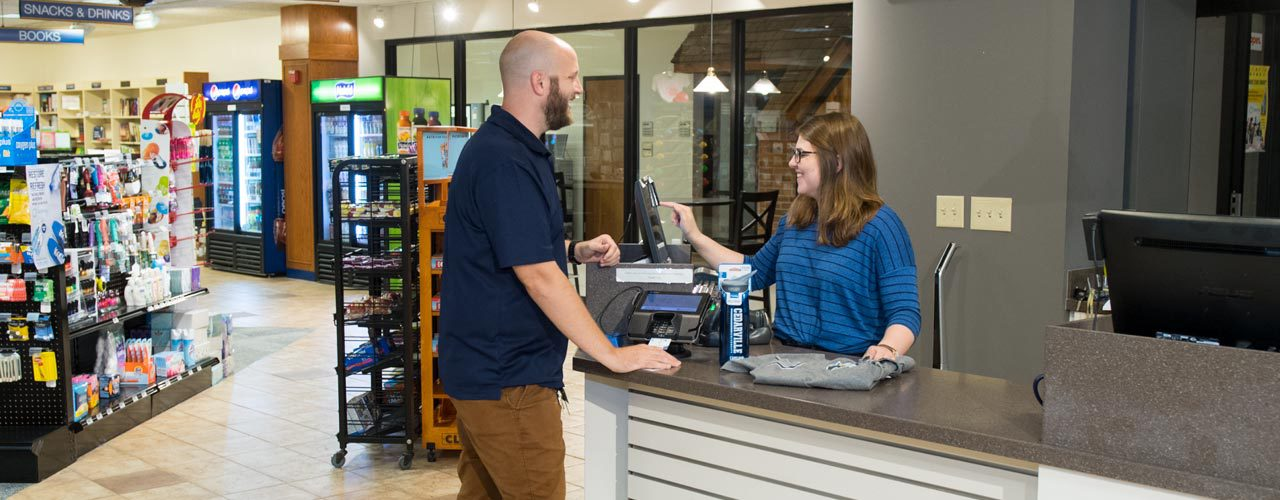 Man buying water bottle in Cedarville University bookstore