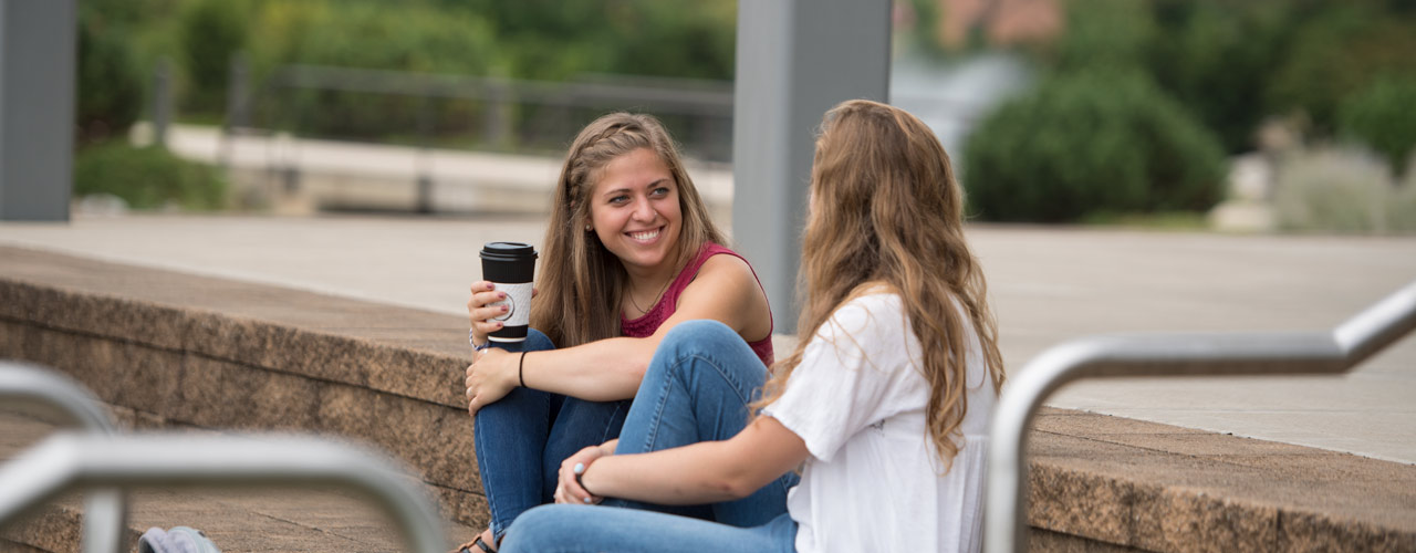 Two female Cedarville students smiling with coffee on stone steps outside of The Center for Biblical and Theological Studies