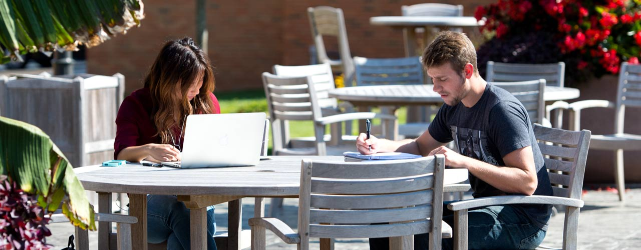 Male and female students studying at a table on the patio at Cedarville