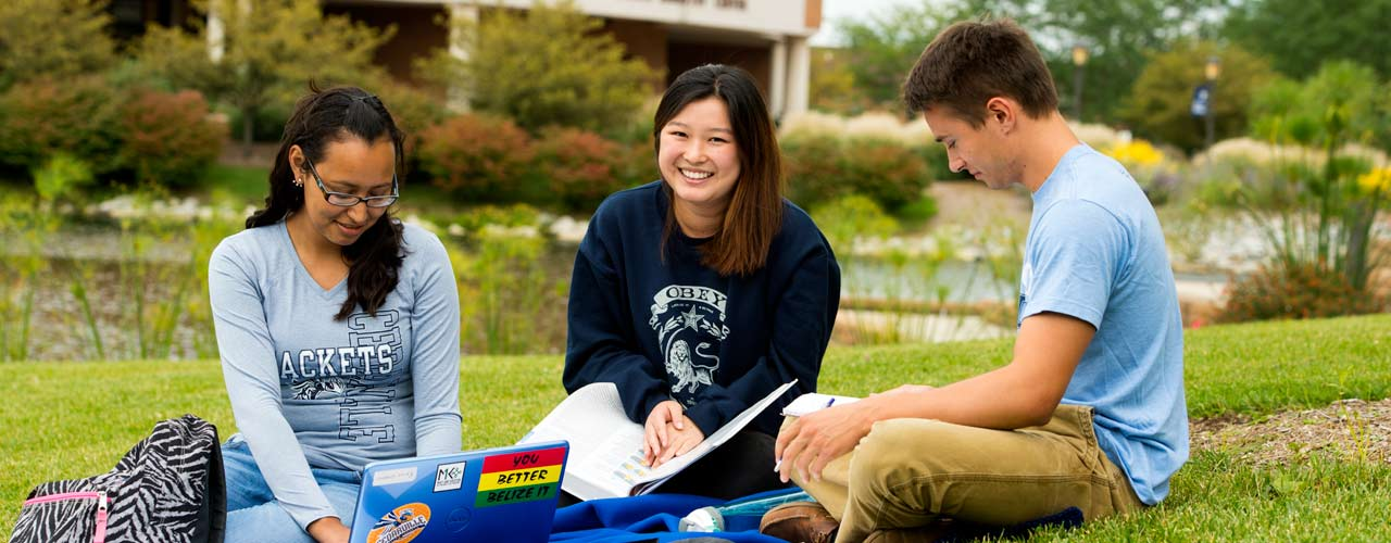 A group of international students studying in the grass by Cedar Lake