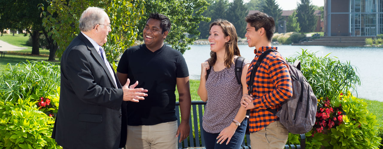 A diverse group of students talk to a professor on Cedarville's beautiful campus