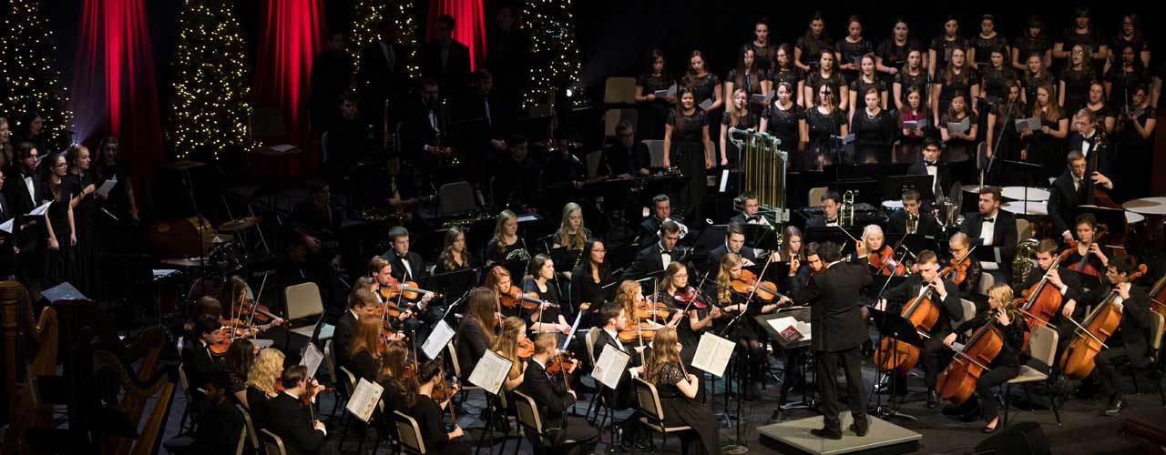 Large orchestra on stage with Christmas decorations all around