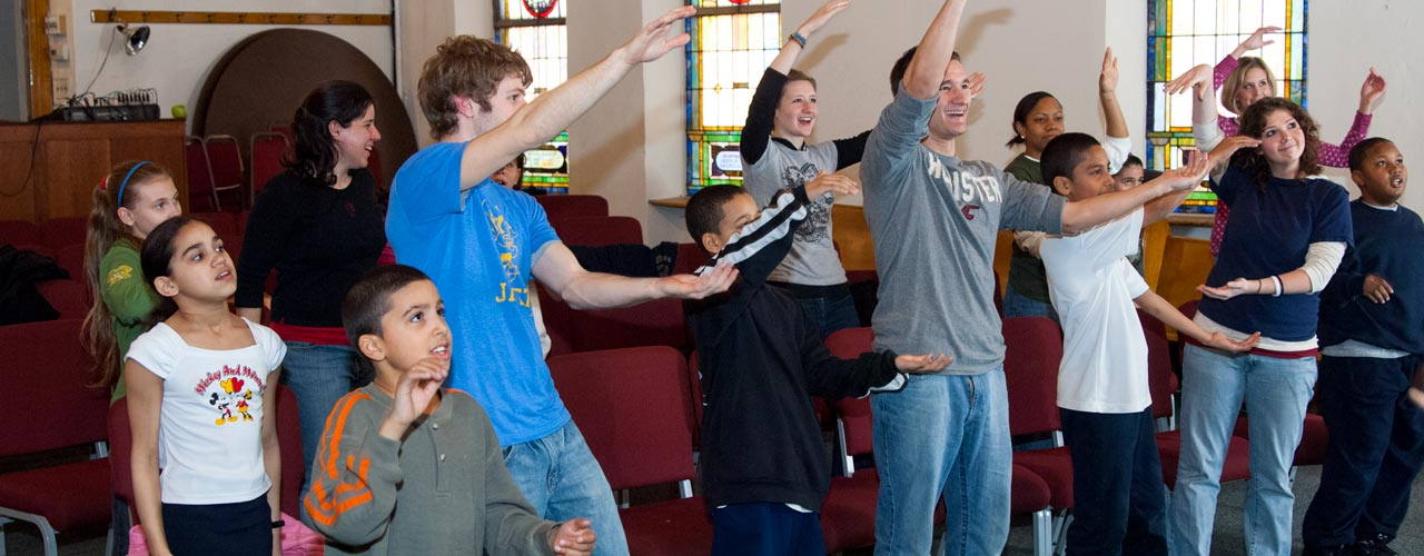 Cedarville Students sing alongside young children at a church service.
