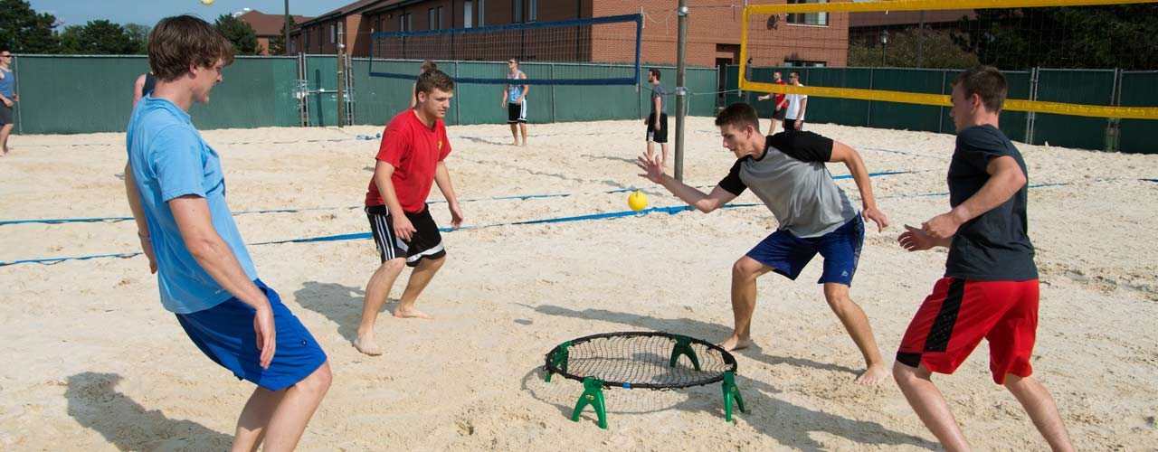 A group of male students play spikeball in a sand volleyball court