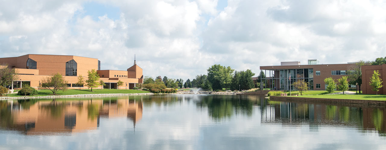 Image of Cedarville campus: Dixon ministry center, Cedar-lake and Biblical and Theological Studies Center are shown on a clear summer day