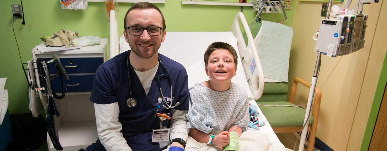 Male nursing student sits with child in a hospital