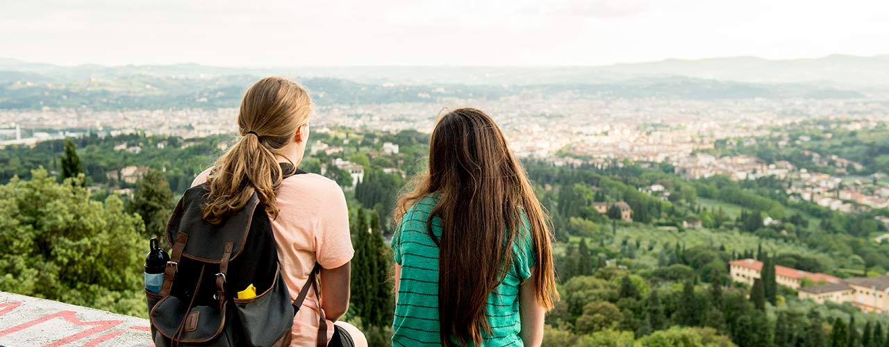 Two female students looking out over a foreign city