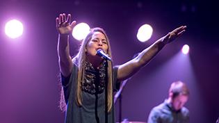 Female worship student sings under purple lights