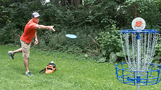 A student throws a disc on Cedarville's disc golf course