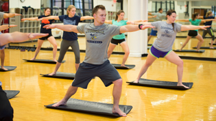A group of male and female students working out in the wood floored exercise studio