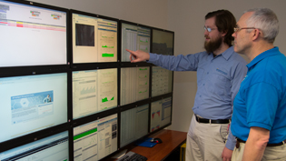 Members of Cedarville's IT staff examining a bank of monitors