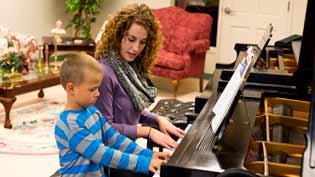 Woman teaches piano young boy