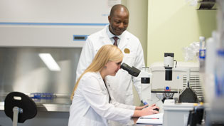 Pharmacy Professor instructs student how to use microscope
