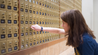 A female student checking her campus post office box.