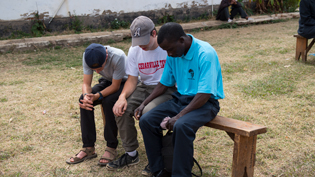 Students on a mission trip pray with a man