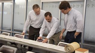 Image of 3 professors looking at Torah Scroll