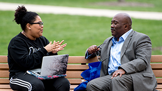 Diverse student and professor discuss together